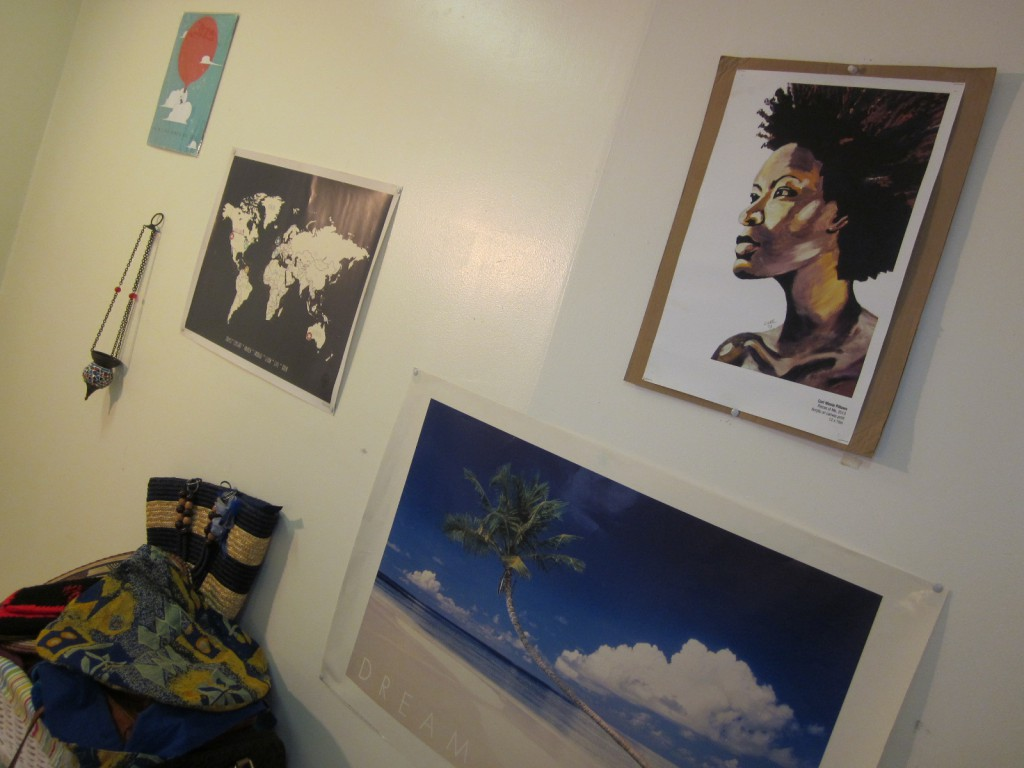 "My travel wall with map, a poster of a beach I would like to visit, Turkish lamp souvenir, painting purchase while travelling, and a poster reminding my that ""not all who wander are lost."""
